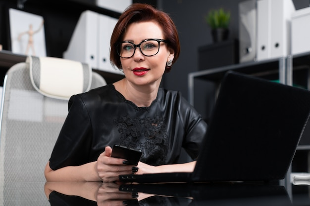 Modieuze vrouw die met laptop en telefoon in bureau werkt
