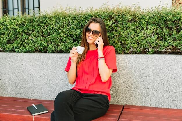 Modieuze vrouw die op cellphone spreekt terwijl het drinken van kop van koffie