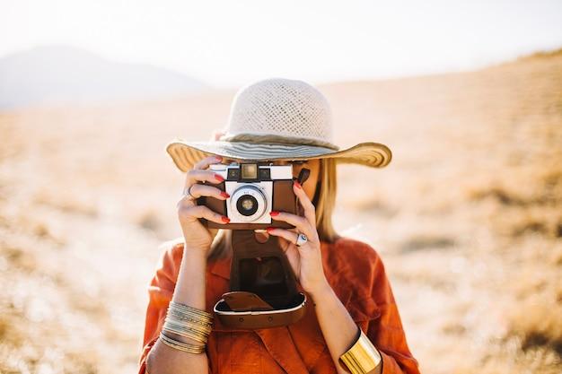 Modieuze vrouw die retro camera in woestijn gebruikt