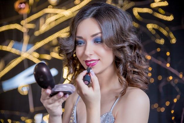 Modieuze vrouw die rode lippenstift zet en in de spiegel kijkt