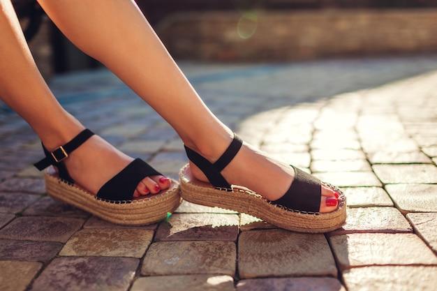 Modieuze vrouw die zwarte de zomerschoenen met strozool in openlucht draagt. comfortabele sandalen. schoonheid mode.
