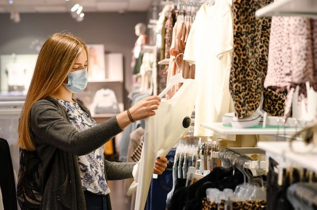 Modieuze vrouw, gekleed in beschermend gezichtsmasker winkelen kleding in heropenen winkel. nieuwe normale levensstijl tijdens pandemie van het coronavirus