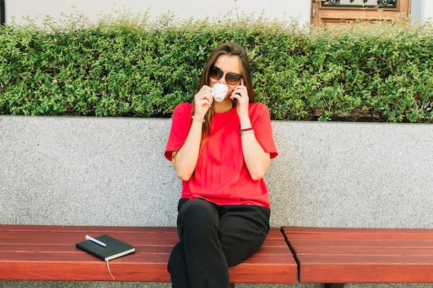 Modieuze vrouw het drinken kop van koffie die op cellphone spreken