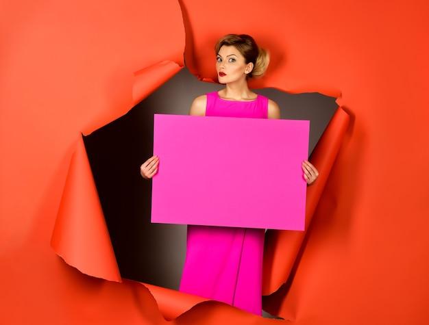 Modieuze vrouw houdt leeg roze bord voor inscriptie tekst. mannequin in roze jurk.