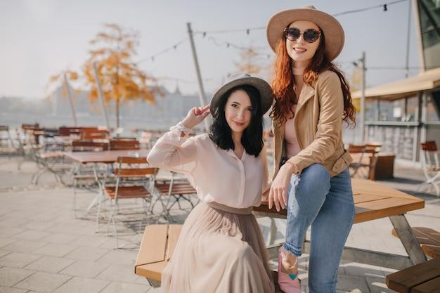 Modieuze vrouw in beige hoed zittend op tafel tijdens fotoshoot met vriend