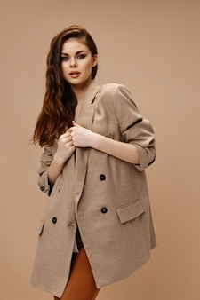 Modieuze vrouw in een jas en sleutelhangers die met haar handen op een beige achtergrond gebaren
