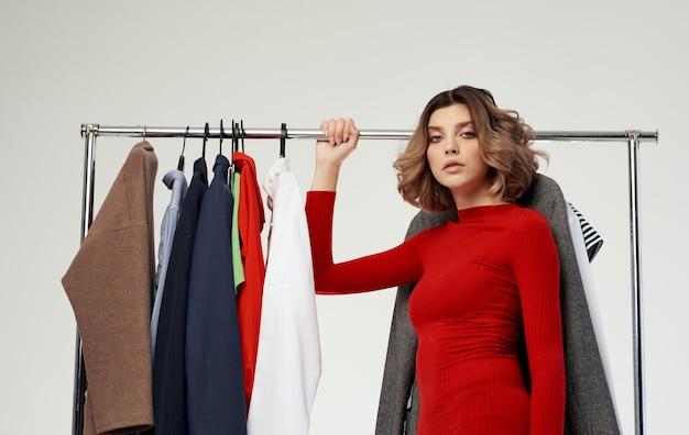 Modieuze vrouw in een rode trui staat in de buurt van een garderobe met shirtkleren winkelen.