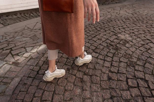 Modieuze vrouw in elegante lange jas in broek in stijlvol schoeisel loopt in de stad. close-up vrouwelijke benen in trendy lederen jeugd sneakers lopen op oude stenen weg. lente damesmode casual schoenen.