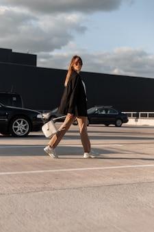 Modieuze vrouw in fashion zonnebril in elegante stijlvolle kleding in trendy sneakers met vintage tas loopt op asfalt tegen blauwe zonnige hemel. aantrekkelijk stedelijk meisjesmodel in jeugdkleren buitenshuis.