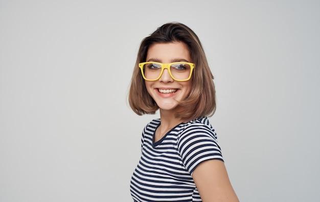 Modieuze vrouw in glazen en in een gestreept t-shirt op een lichte muurrode rok.