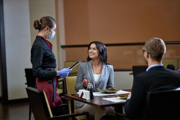 Modieuze vrouw in grijs pak zit met man aan tafel en vraagt serveerster om iets terwijl ze handgebaar maakt