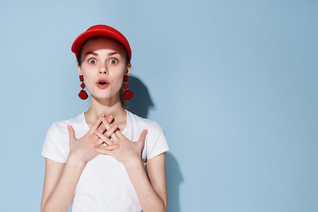 Modieuze vrouw in rode dop oorbellen poseren glamour blauwe achtergrond