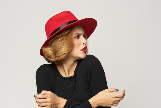 Modieuze vrouw in rode hoed zwarte blouse rode lippen bijgesneden weergave lichte ruimte emoties.