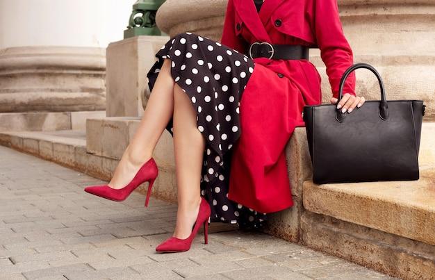 Modieuze vrouw in rode jas, hielschoenen, zwarte tas. outdoor herfst- en lente-outfit