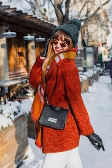 Modieuze vrouw in stijlvolle winteroutfit die door de stad loopt