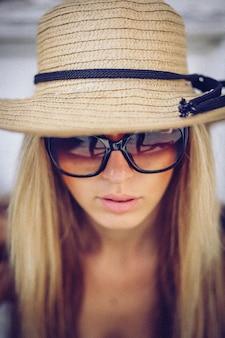 Modieuze vrouw in witte hoed die zich op oude stad bevindt