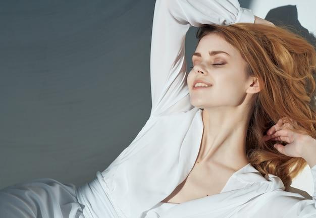 Modieuze vrouw in witte jurk leunt op de muur levensstijl romantiek