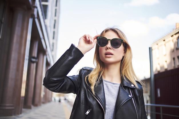 Modieuze vrouw in zonnebril op straat praten aan de telefoon