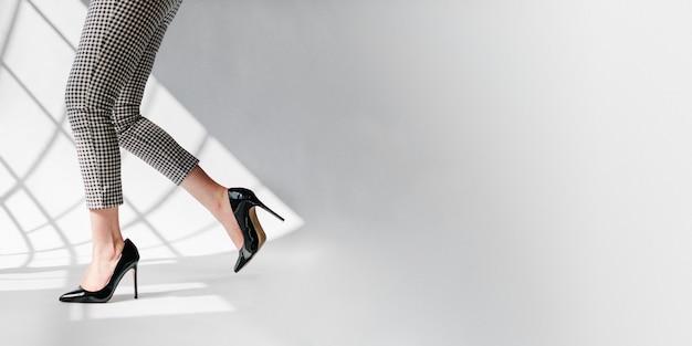 Modieuze vrouw in zwarte glanzende hakken sociale banner