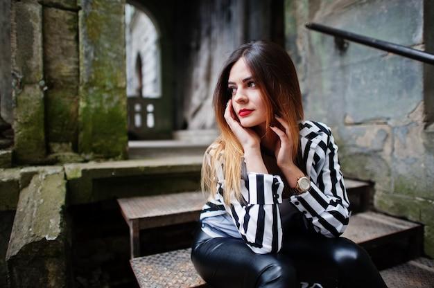 Modieuze vrouw kijkt met zwart en wit gestreept colbert, lederen broek, die zich voordeed op oude straat op ijzeren trappen