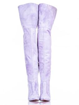 Modieuze vrouw laarzen geïsoleerd op een witte achtergrond. mooie paarse hoge dameslaarzen. luxe.