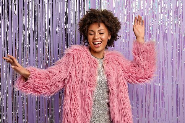 Modieuze vrouw met afro kapsel dansen in club, heeft plezier in disco, gekleed in stijlvolle kleding