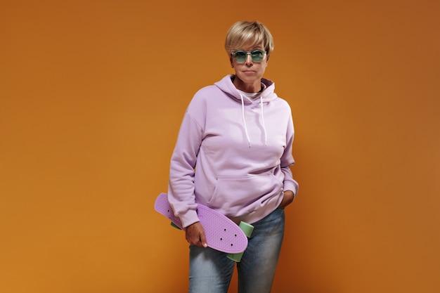 Modieuze vrouw met blond haar en groene bril in roze hoodie en spijkerbroek koel skateboard te houden en op zoek naar camera.