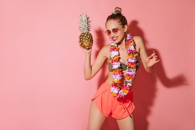 Modieuze vrouw met charmante glimlach in zonnebril, korte broek, zwempak en heldere ketting van bloemen dansen met ananas op roze muur