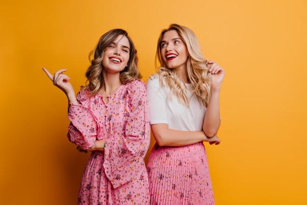 Modieuze vrouw met golvend haar tijd doorbrengen met zus. tevreden vriendinnen die zich op gele muur bevinden.