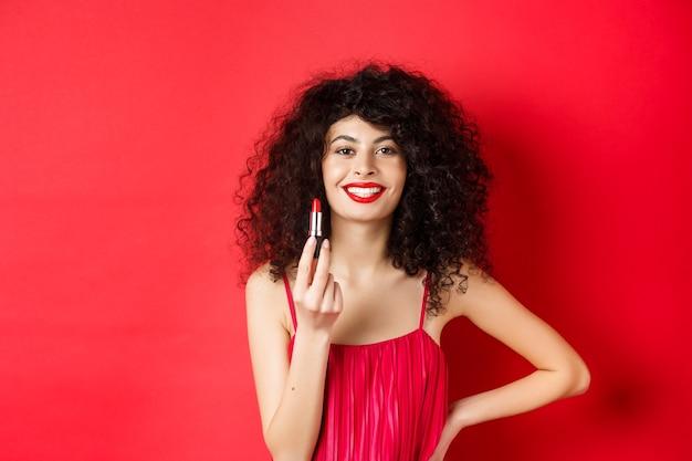 Modieuze vrouw met krullend haar, rode lippenstift tonen en glimlachen, cosmetica aanbevelen, staande op een witte achtergrond.