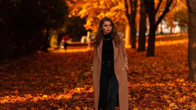 Modieuze vrouw met rode lippen in een stijlvolle beige jas met een zwarte trui loopt in een herfstpark met oranje bladeren bij zonsondergang