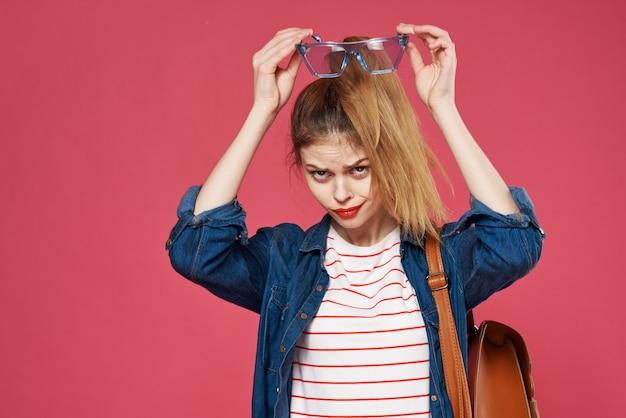 Modieuze vrouw met rugzak kleren student leren roze achtergrond