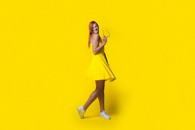 Modieuze vrouw met sproeten en rood haar in een gele jurk is poseren met bril glimlachend in de camera op studio muur