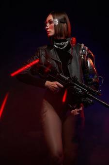 Modieuze vrouw met stijlvol kapsel in zwarte kleding poseert met een futuristisch geweer. mooie vrouwelijke soldaat in cyberpunkstijl.