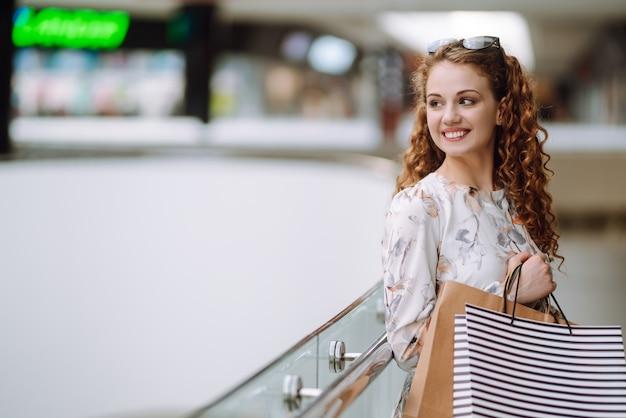 Modieuze vrouw met veelkleurige tassen in het winkelcentrum. de vreugde van consumptie.
