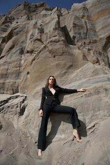 Modieuze vrouw poseren in de buurt van de zanderige rotsen