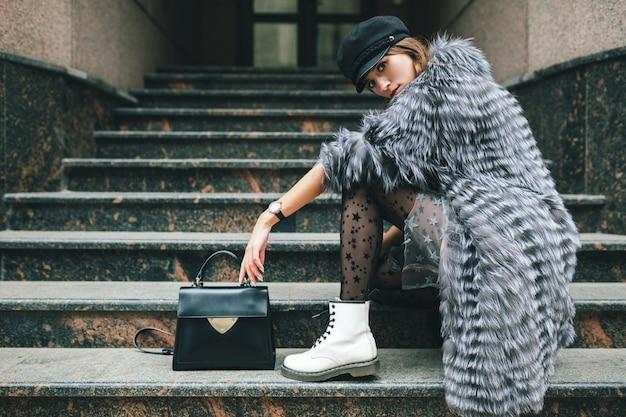 Modieuze vrouw poseren in de stad in warme bontjas, winterseizoen, koud weer, zwarte pet, jurk, witte laarzen, lederen tas, straat modetrend dragen