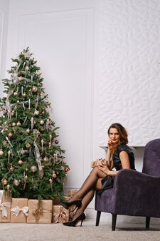 Modieuze vrouw poseren in fauteuil in de buurt van kerstboom en open haard, benen in ouderwetse kousen tonen