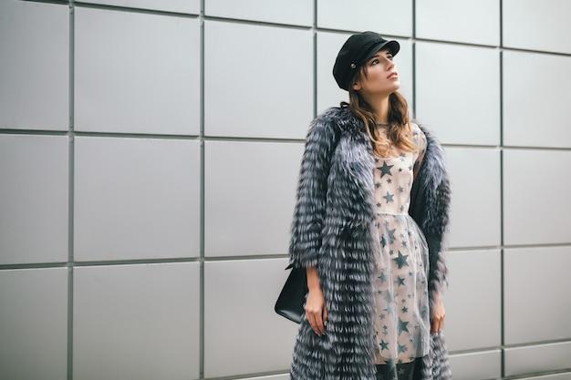 Modieuze vrouw wandelen in de stad in warme bontjas en feestjurk, winterseizoen accessoires