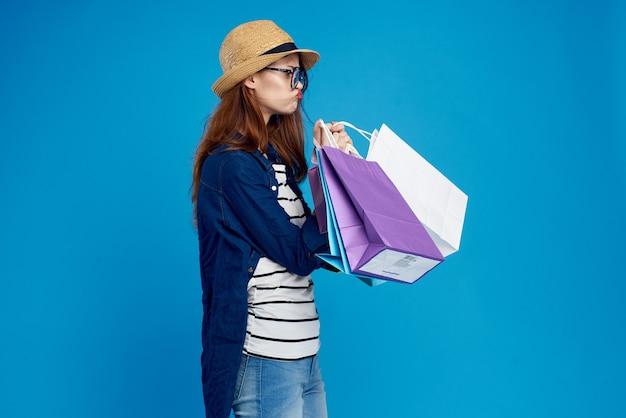 Modieuze vrouw winkelt met pakketten op een blauw in een gestreept t-shirt en jasje