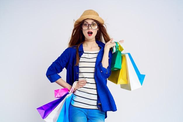 Modieuze vrouw winkelt met pakketten op een lichte achtergrond in een gestreept t-shirt, bril op haar gezicht