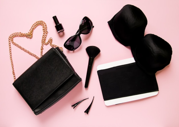 Modieuze vrouwelijke accessoires op zacht roze achtergrond. koppeling, zonnebril, nagellak, beha, make-upborstel, spray, spelden en andere.