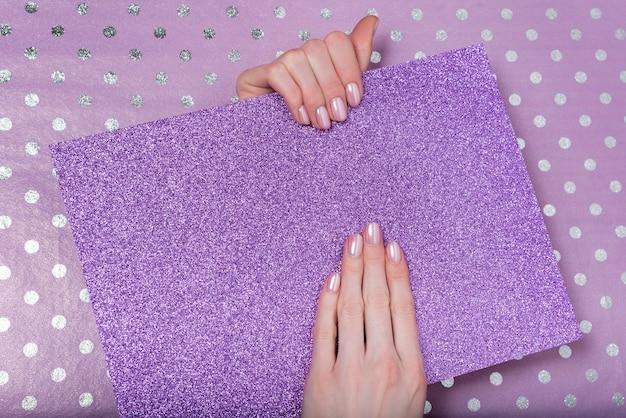 Modieuze vrouwelijke manicure, delicate roze kleur. glanzend paars