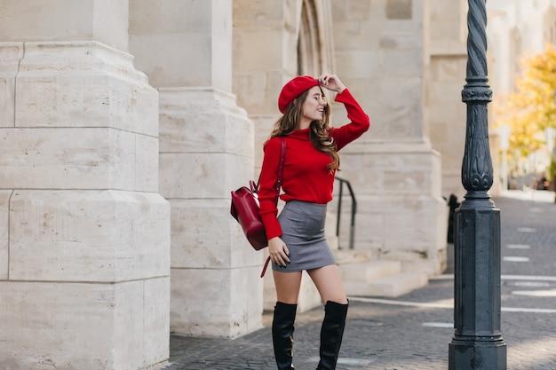 Modieuze vrouwelijke toerist in kniehoge laarzen die de attracties van europa verkennen