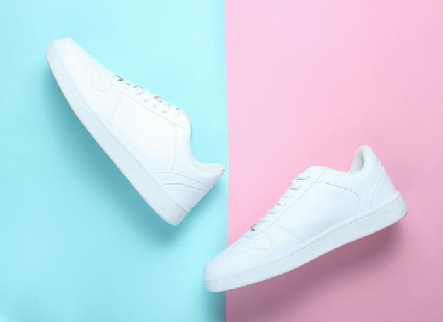 Modieuze witte sneakers op een gekleurde pasteltafel, minimalisme, bovenaanzicht, creatieve lay-out, stap