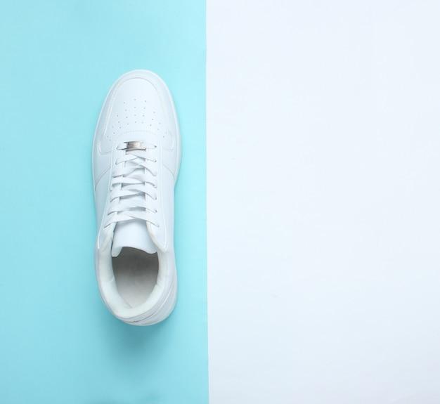 Modieuze witte sneakers op een gekleurde pasteltafel, minimalisme, bovenaanzicht, creatieve lay-out