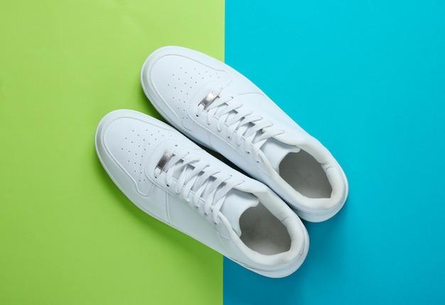 Modieuze witte sneakers op een tweekleurige tafel. bovenaanzicht