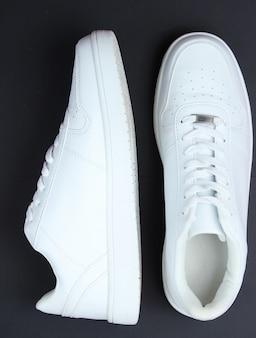 Modieuze witte sneakers op een zwarte tafel. bovenaanzicht
