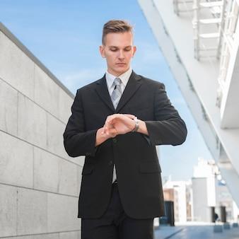 Modieuze zakenman die horloge bekijkt