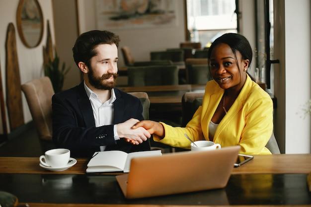 Modieuze zakenman die in een bureau met partner werkt